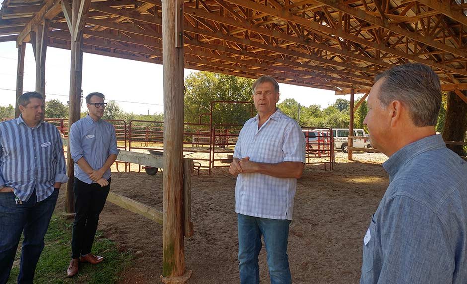 Trace Emby in a covered outdoor horse barn talking to local pastors